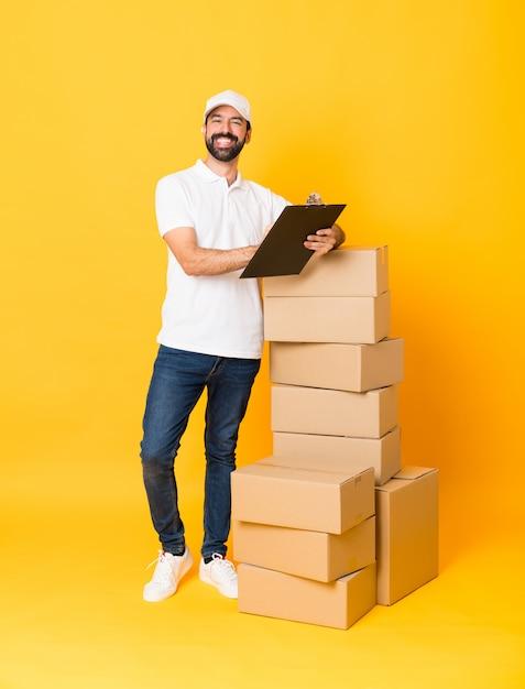 Tiro completo do entregador entre caixas sobre amarelo isolado Foto Premium