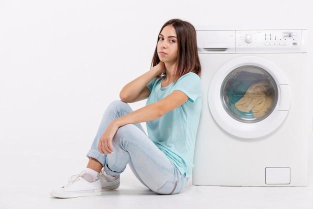 Tiro completo entediada mulher sentada perto da máquina de lavar roupa Foto Premium
