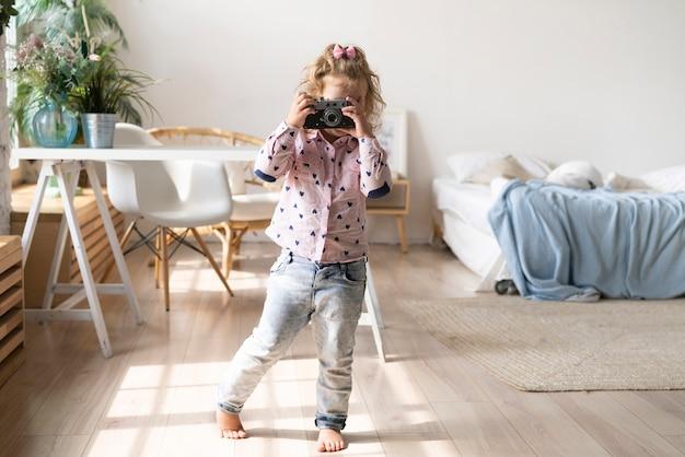 Tiro completo garota tirando fotos com a câmera Foto gratuita