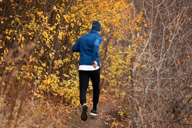 Tiro completo homem correndo na trilha na floresta Foto gratuita