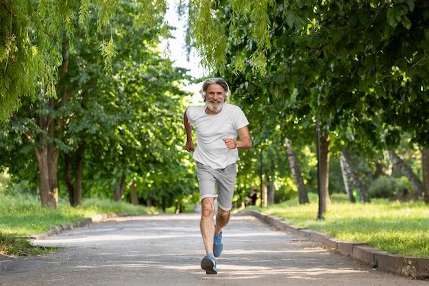 Tiro completo homem correndo no parque Foto Premium
