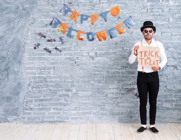 Tiro completo homem segurando doces ou travessuras sinal para o halloween Foto gratuita