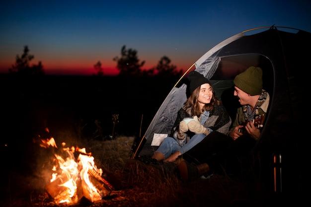 Tiro completo jovem casal se aquecendo à noite Foto gratuita