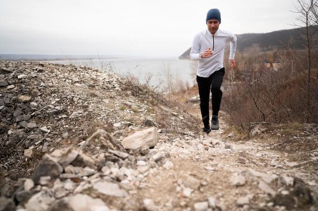 Tiro completo jovem macho correndo na trilha Foto Premium