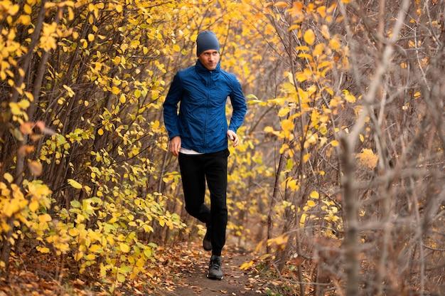 Tiro completo masculino correndo na trilha na floresta Foto gratuita