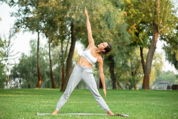 Tiro completo mulher exercitando na natureza Foto gratuita