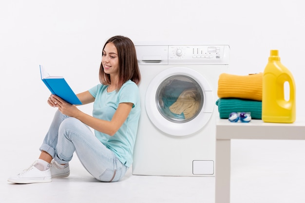 Tiro completo mulher lendo perto de máquina de lavar roupa Foto Premium