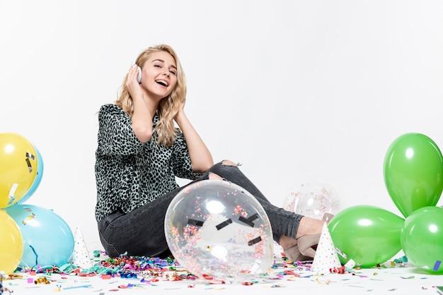 Tiro completo, mulher, ouvindo música, cercado por balões Foto gratuita