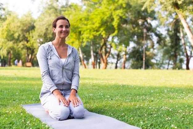 Tiro completo mulher sorridente no tapete de ioga Foto gratuita