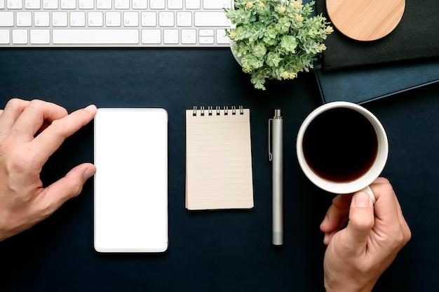 Tiro da mão do homem que toca na tela do smartphone e que guarda a xícara de café ao trabalhar no escritório. Foto Premium