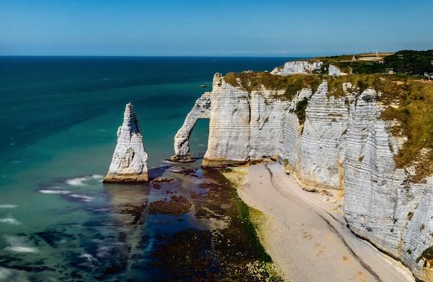 Tiro de alto ângulo de falésias na costa do oceano azul-turquesa Foto gratuita