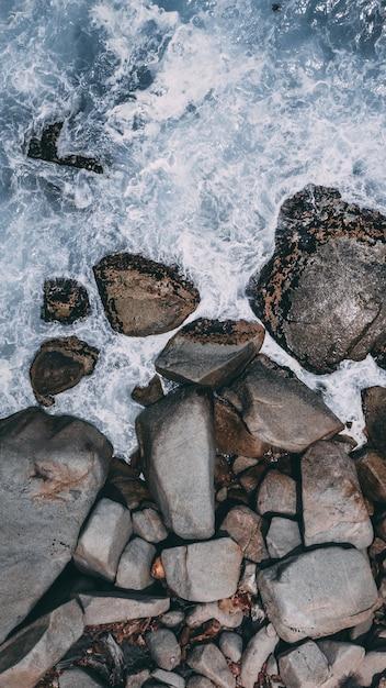 Tiro de alto ângulo vertical de grandes pedras na água do oceano tempestuoso Foto gratuita