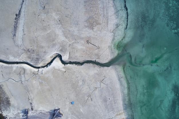 Tiro de ângulo alto de uma grande rachadura na costa pedregosa ao lado da água turquesa Foto gratuita