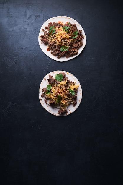 Tiro de ângulo alto vertical de dois tortilla pão com carne e queijo derretido em uma superfície preta Foto gratuita