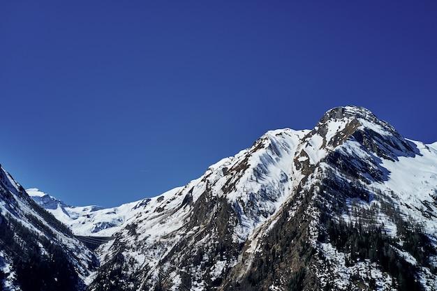 Tiro de ângulo baixo bonito de uma montanha com neve cobrindo o pico e o céu ao fundo Foto gratuita