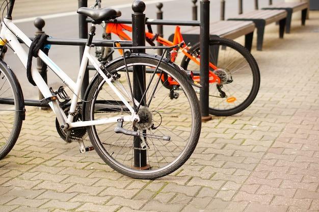 Tiro de ângulo baixo closeup de duas bicicletas estacionadas na calçada Foto gratuita