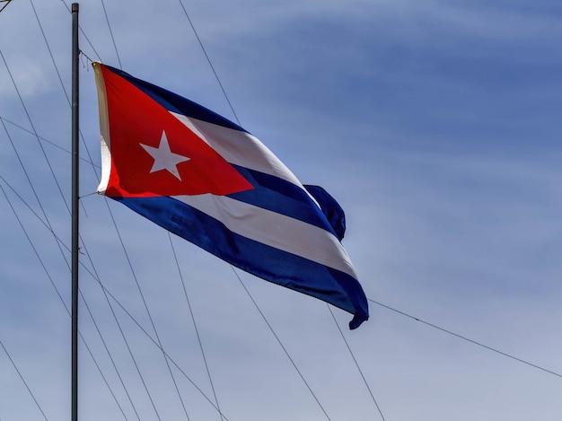 Tiro de ângulo baixo da bandeira nacional de cuba em um mastro de bandeira Foto gratuita