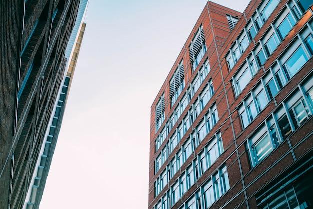 Tiro de ângulo baixo de edifícios de apartamentos de concreto com muitas janelas Foto gratuita