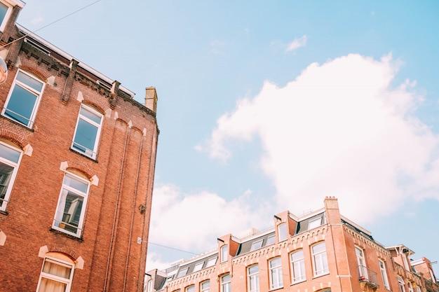 Tiro de ângulo baixo de edifícios de concreto marrons sob o céu nublado Foto gratuita