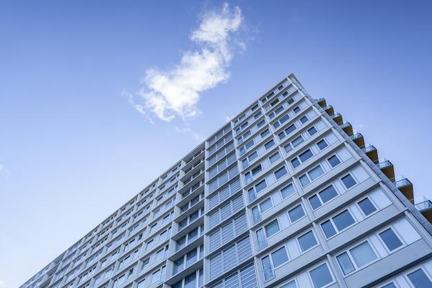 Tiro de ângulo baixo de um grande edifício sob uma nuvem no lindo céu azul Foto gratuita