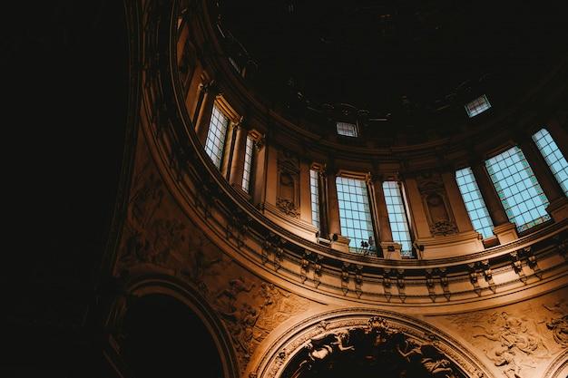 Tiro de ângulo baixo de um interior de igreja com arte medieval hipnotizante Foto gratuita
