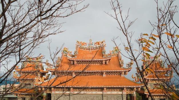 Tiro de ângulo baixo do santuário xintoísmo com texturas interessantes sob o céu claro Foto gratuita