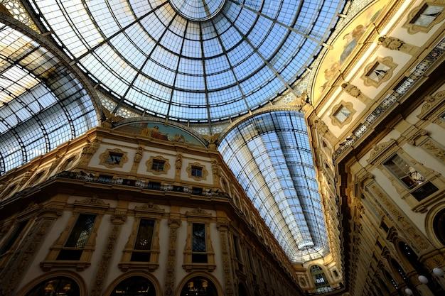 Tiro de ângulo baixo do teto de vidro com paredes brancas e douradas com fotos Foto gratuita