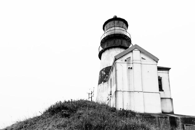 Tiro de ângulo baixo em escala de cinza de um farol perto de uma pequena cabana em um penhasco Foto gratuita