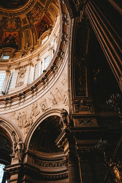 Tiro de ângulo baixo vertical das belas pinturas e esculturas em um prédio antigo Foto gratuita