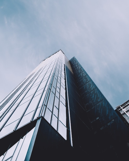Tiro de ângulo baixo vertical de um prédio alto em uma fachada de vidro Foto gratuita