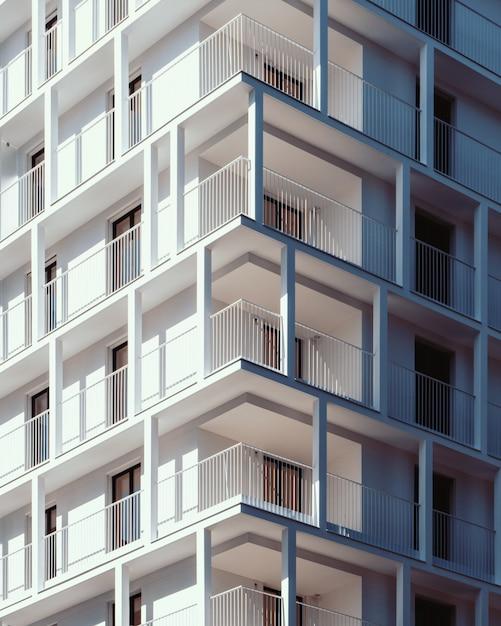 Tiro de ângulo baixo vertical de um prédio de concreto branco de arranha-céus Foto gratuita