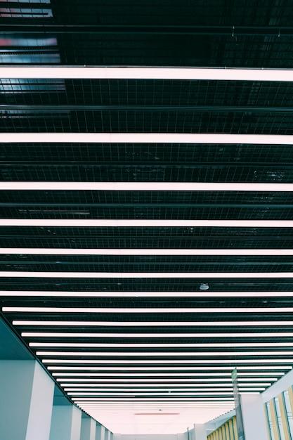Tiro de ângulo baixo vertical de um teto em um corredor com ilustrações brancas Foto gratuita