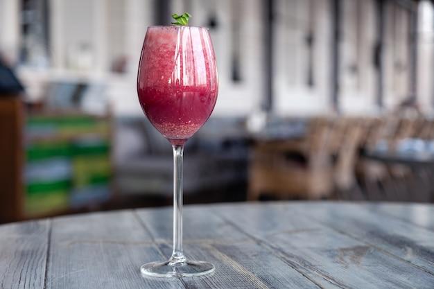Tiro de comida. berry cocktail em copo de cristal decorado hortelã, frutas, romã, laranja, abacaxi. Foto Premium