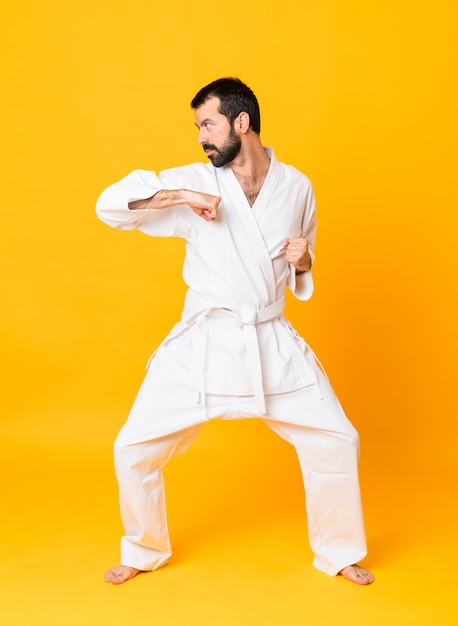 Tiro de corpo inteiro de karatê de combate sobre fundo amarelo isolado Foto Premium