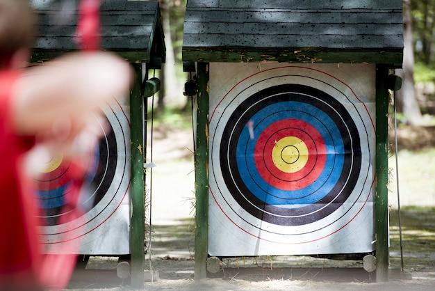 Tiro de foco seletivo de um alvo com uma pessoa borrada usando arco e flecha Foto gratuita