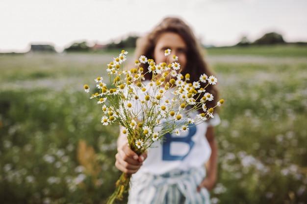 Tiro de foco seletivo de um modelo encaracolado em pé em um campo segurando um buquê de margaridas Foto gratuita