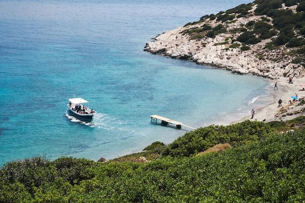 Tiro de fotografia aérea de um barco se aproximando da pequena praia de amorgos, grécia Foto gratuita