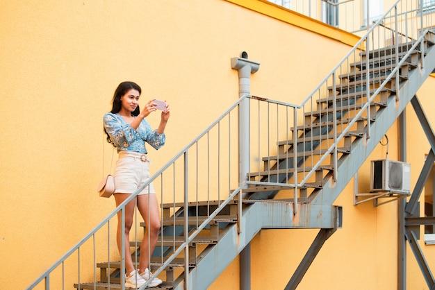 Tiro de mulher em pé na escada e tirar fotos Foto gratuita