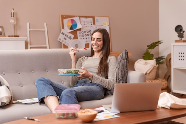 Tiro de mulher trabalhando e comendo Foto gratuita