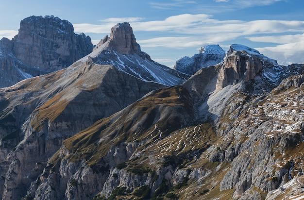 Tiro de tirar o fôlego de rochas nevadas nos alpes italianos sob o céu brilhante Foto gratuita