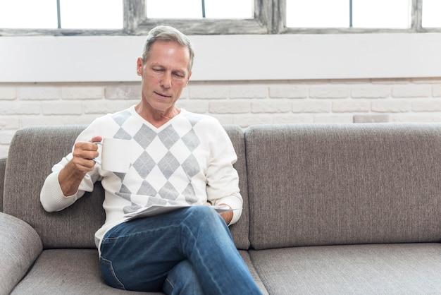 Tiro de tiro médio homem lendo no sofá Foto gratuita