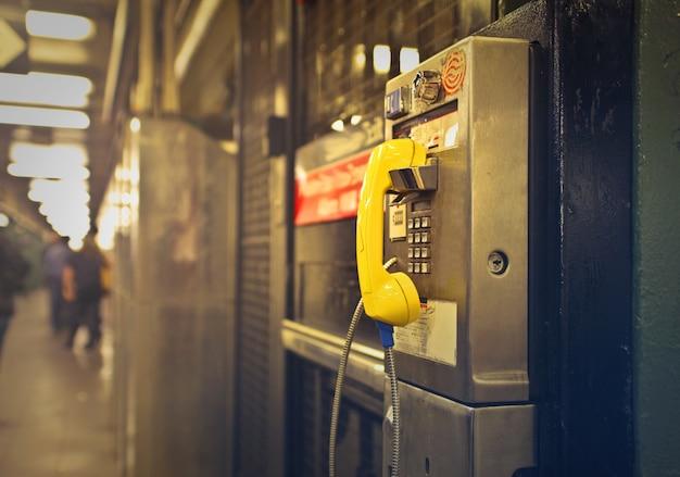 Tiro de um telefone público amarelo e cinza Foto gratuita