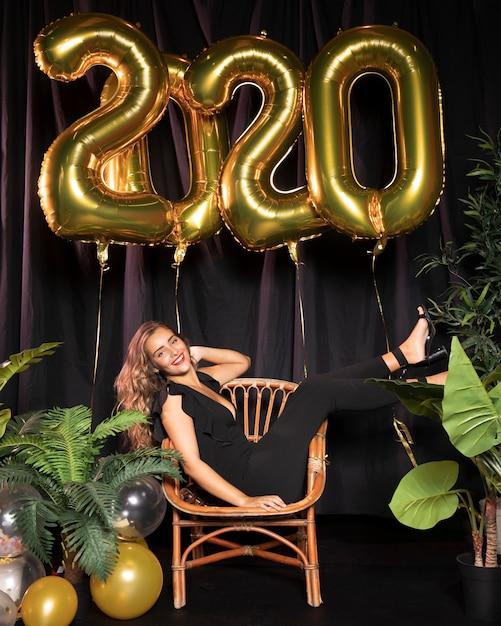 Tiro de uma mulher em um terno preto festa de ano novo 2020 Foto gratuita