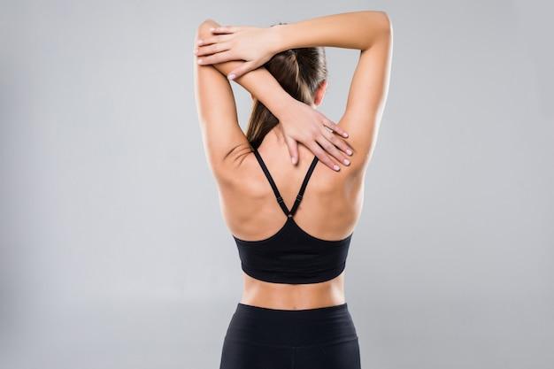 Tiro de vista traseira de uma jovem saudável no sportswear isolado na parede branca Foto gratuita