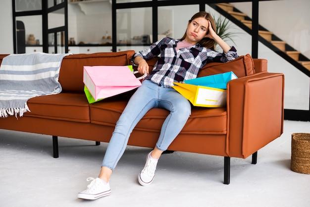 Tiro desapontado mulher sentada no sofá com sacos Foto gratuita