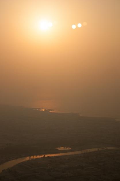 Tiro distante de um rio que flui perto de uma cidade durante o dia com um sol brilhando no céu Foto gratuita