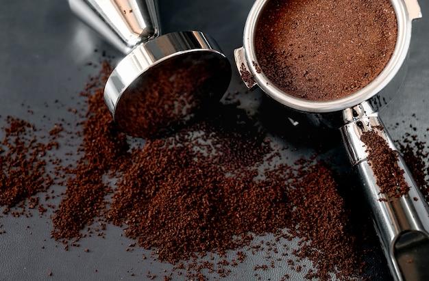 Tiro do close up do portafilter com café e adulteração no fundo de couro preto Foto Premium