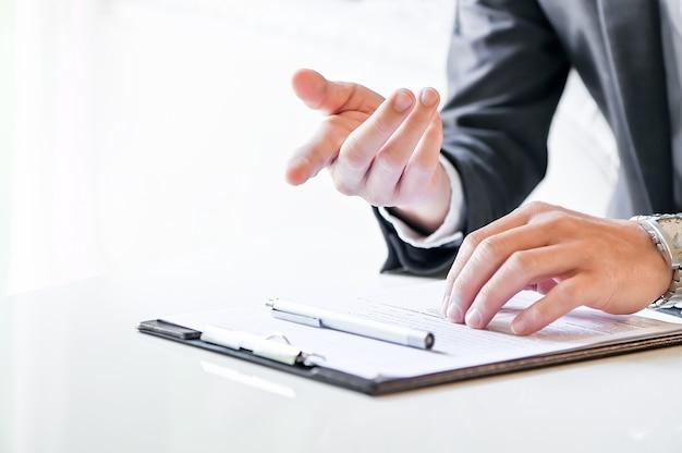 Tiro do empresário mão apontando para a frente enquanto está sentado na mesa branca Foto Premium