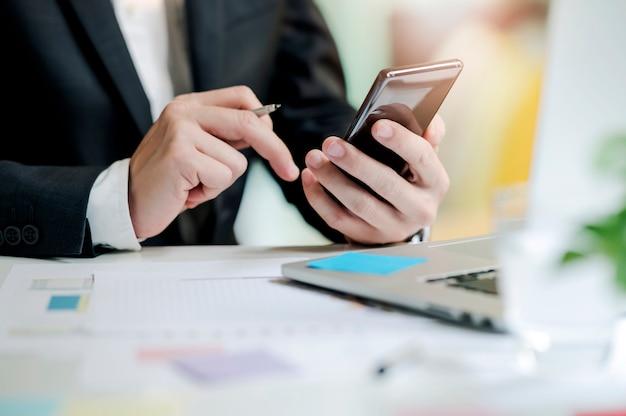 Tiro do homem de negócios que trabalha no escritório, pena de terra arrendada e usando o smartphone. Foto Premium