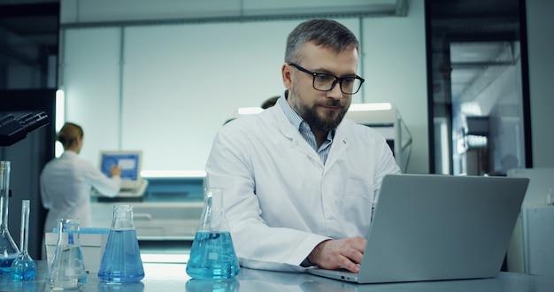 Tiro do retrato do homem caucasiano de óculos e roupão branco, trabalhando no computador portátil no laboratório ao lado com um microscópio. Foto Premium